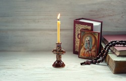 burning candle, orthodox icon, rosary beads, bible books. concept of faith, God, Church, lent. copy space. selective focus