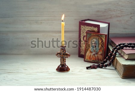 burning candle, orthodox icon, rosary beads, bible books. concept of faith, God, Church, lent. copy space. selective focus Foto d'archivio ©