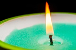 Burning candle wick with green wax close-up on black background. Macro shooting.