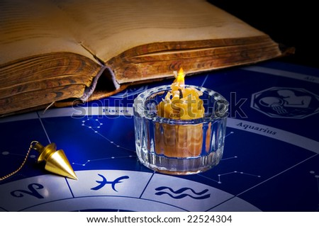 burning candle with a magic pendulum and old book on an astrological background