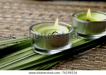 Burning candle with bamboo leaves. on natural straw background