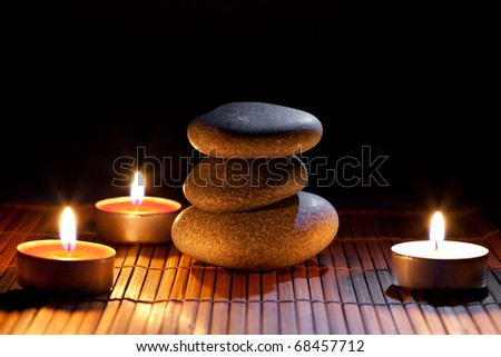 Burning candles and and a stack of pebbles