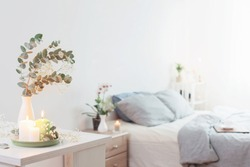 burning candles and eucalyptus in  vase in white bedroom