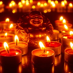 Burning candles and figurine of Lucky Buddha. Focus on the front candles