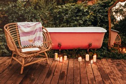 Burning candles and wicker chair with book and wine placed on wooden path near bathtub and mirror in garden