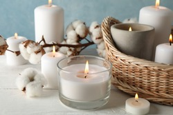 Burning candles, basket and cotton on white wooden table, close up