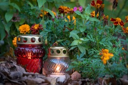 Burning candles for the Day of the Dead surrounded by flowers. Autumn Christian festival. All Saints' Day in Poland, decorations for the cemetery.