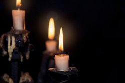 Burning candles in a candlestick on a dark background.