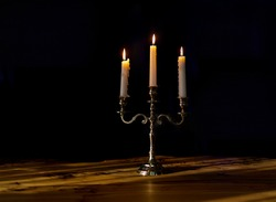 burning candles in candelabra on a black background, close-up