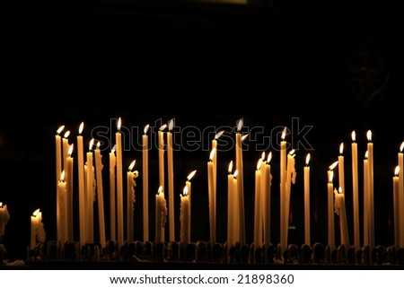 Burning candles in cathedral Duomo in Milan