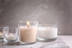 Burning candles in glasses on marble table