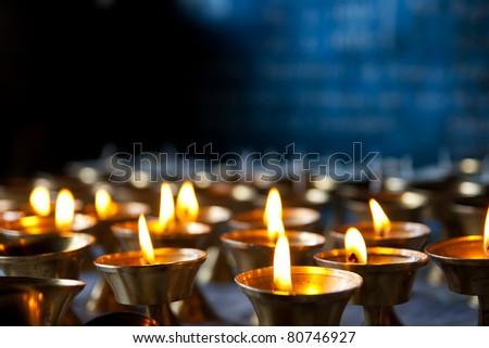 Burning candles in sconces on black blue background