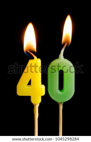 Burning candles in the form of 40 forty figures (numbers, dates) for cake isolated on black background. The concept of celebrating a birthday, anniversary, important date, holiday