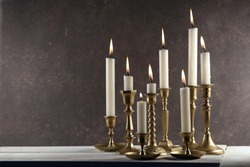 Burning candles in vintage metal candlesticks on white wooden table against dark stone background with copy space.