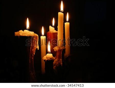 Burning candles isolated on black background