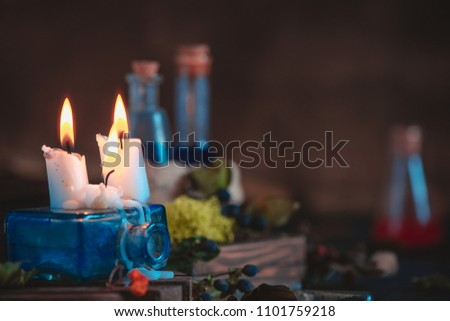 Burning candles on an inkwell in a magical still life with potions and moss. Witchcraft concept with copy space. #1101759218