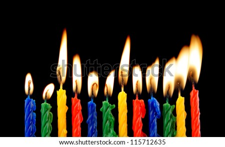 Burning candles on black background - stock photo