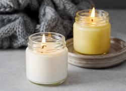 Burning candles on grey table, space for text. Grey knitted scarf and scented candles. Cozy winter atmosphere. 2021. Сolors of the year. burning candles on a gray background. New Year. Romantic.