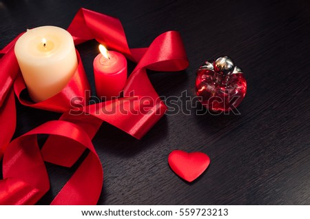 Burning candles, wrapped in red ribbon. With a heart and a bottle of perfume. Gift for Valentine's Day. Dark texture with a romantic symbol of love by fourteen february. #559723213