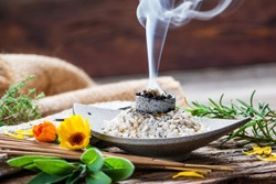 Burning charcoal and incense sticks with frankincense, sage, thyme and marigold attractively decorated against a rustic and traditional background