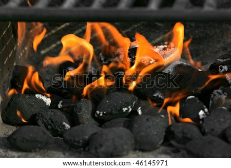 burning charcoal biscuits set on fire in a barbecue grill - stock photo