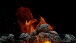 Burning charcoal isolated on black background. Free space for text.