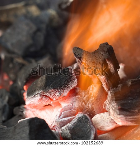 Burning charcoal with orange-colored flame and glow (Selective Focus, Focus on parts of the charcoal pieces around the flame)