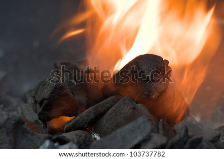 Burning charcoal with orange-colored flame and smoke (Selective Focus, Focus on the front of the big charcoal piece in the middle of the flame)