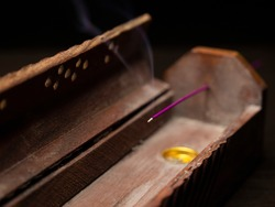 Burning chinese incense in wooden incense holder