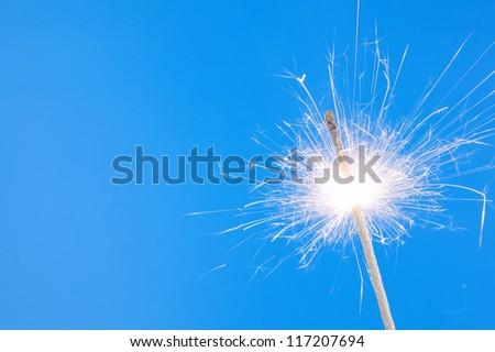 Burning christmas sparkler on blue background with room for text