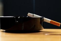 Burning cigarette in a black ash tray