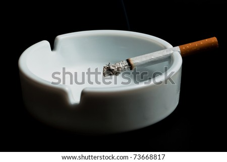 burning cigarette in the ashtray white on black background