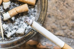 Burning cigarette on a glass ashtray full of ash and cigarette butts