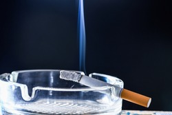 Burning cigarette smoke in glass ash-tray dark background copy space, tobacco smoking