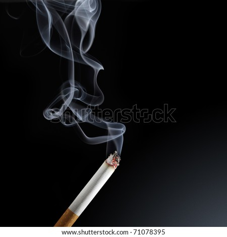 Burning cigarette with smoke on black background