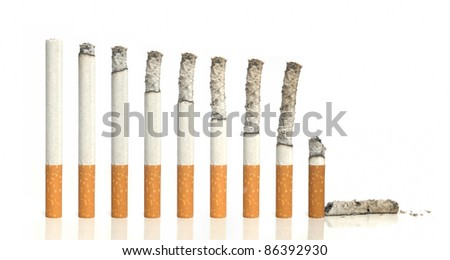 Burning cigarettes in a row on white background