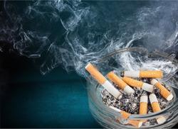 Burning cigarettes in ashtray on white background