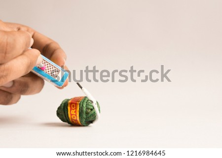 Burning crackers with hand concept using matchstick on isolated background  #1216984645