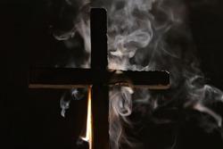 Burning cross with smoke in dark night