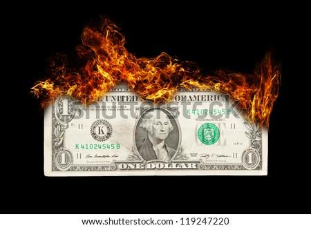 Burning dollar bill symbolizing careless money management and the phrase money to burn - stock photo