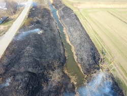 Burning dry grass along the irrigation canal. Smoke and the flame of dry grass. Burnt dry grass