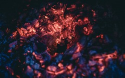 Burning embers of the fireplace after the fire. Glowing incandescent embers texture. close up.