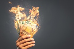 Burning Euro banknotes held by a hand