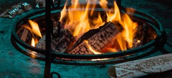 Burning Fire. Street food.Closeup. Bonfire,burning trees logs.Fried chicken meat,Shaverma,Doner kebab.Warm,cozy.Red,orange fire flame,smoke.The chef cooks the meat over an open fire.Diner in the city.