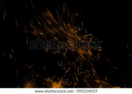 Burning fire with fiery orange flames, sparks and embers exploding into the air on a dark background with copy space