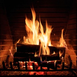 Burning fireplace. Cozy warm home, christmas time. Wood logs fire glowing in the dark. Closeup view