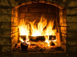 Burning firewood in fire-box of fireplace in country cottage. Rustic cooking oven with burning logs.