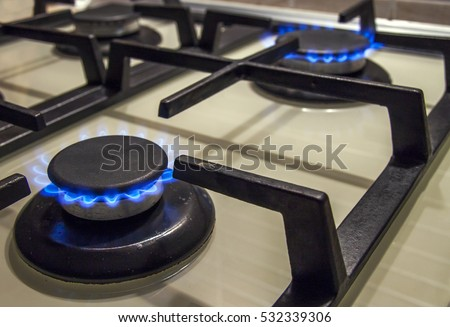 Burning gas stove hob blue flames close up in the dark on a black background stock photo