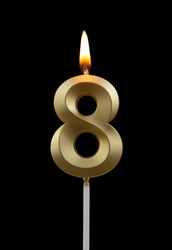 Burning golden birthday candle isolated on black background, number 8