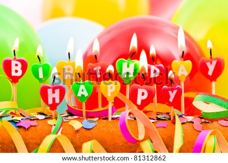 burning happy Birthday candles with balloons and confetti